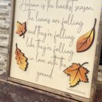 a cream background wood sign with dark brown wood frame with brown cursive font lettering and 2 layered laser cut leaves colored in gold and orange leaves to add dimension