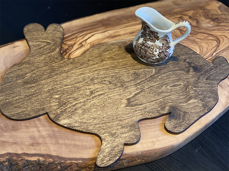wood cut shaped bunny stained dark brown with a brown and white transferware creamer placed on top