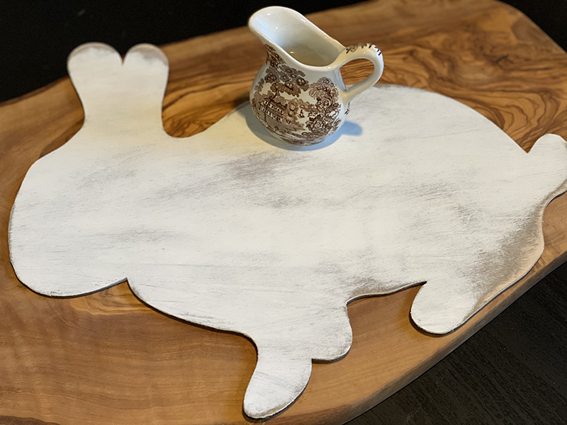 wood cut shaped bunny painted white and distressed with a brown and white transferware creamer placed on top